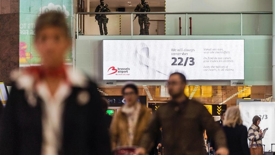 Soldiers patrol as passengers walk through the departure terminal, marking the one-year anniversary service at Zaventem Airport in Brussels on Wednesday, March 22, 2017. The suicide bombings at the Brussels airport and subway on March 22, 2016, killed 32 people and wounded more than 300 others. (AP Photo/Geert Vanden Wijngaert)