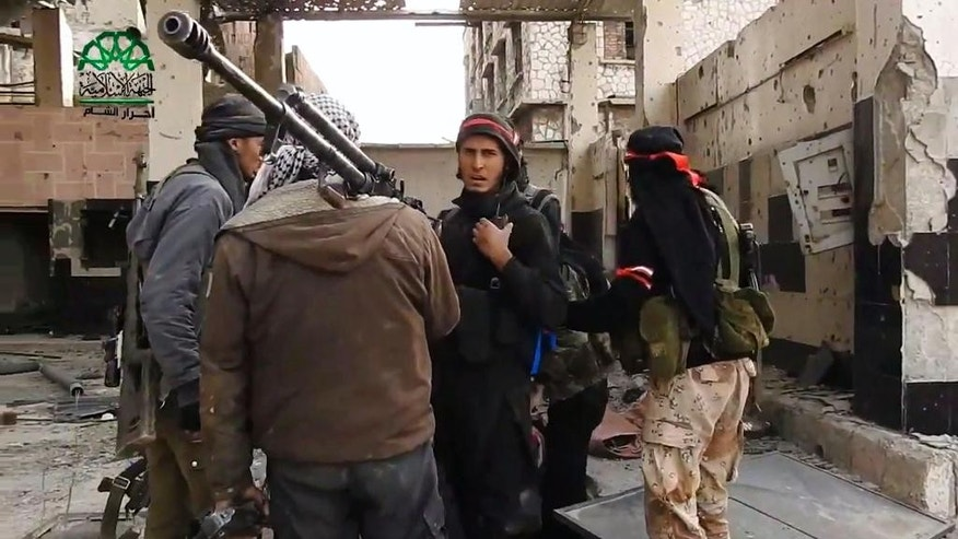 This frame grab from video provided on Tuesday March 21, 2017, by Ahrar al-Sham, Syrian militant group outlet that is consistent with independent AP reporting, shows fighters from Ahrar al-Sham militant group gather during a battle against Syrian government forces, in an eastern neighborhood of Damascus, Syria. Syrian government forces launched a counter-attack against rebels in Damascus on Tuesday, following a rebel suicide car bombing and another insurgent assault earlier in the day in the country's capital, media reports said. (Ahrar al-Sham, Syrian militant group, via AP)