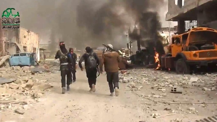 This frame grab from video provided on Tuesday March 21, 2017, by Ahrar al-Sham, Syrian militant group outlet that is consistent with independent AP reporting, shows fighters from Ahrar al-Sham militant group run next of a burn truck during a battle against the Syrian government forces, in an eastern neighborhood of Damascus, Syria. Syrian government forces launched a counter-attack against rebels in Damascus on Tuesday, following a rebel suicide car bombing and another insurgent assault earlier in the day in the country's capital, media reports said. (Ahrar al-Sham, Syrian militant group, via AP)