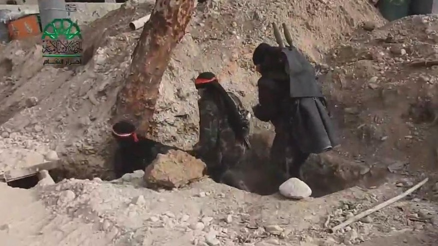 This frame grab from video provided on Tuesday March 21, 2017, by Ahrar al-Sham, Syrian militant group outlet that is consistent with independent AP reporting, shows fighters from Ahrar al-Sham militant group enter a trench during a battle against the Syrian government forces, in an eastern neighborhood of Damascus, Syria. Syrian government forces launched a counter-attack against rebels in Damascus on Tuesday, following a rebel suicide car bombing and another insurgent assault earlier in the day in the country's capital, media reports said. (Ahrar al-Sham, Syrian militant group, via AP)