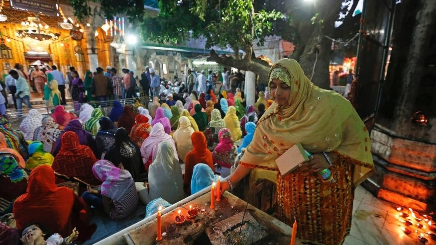 An Indian woman lights a candle during daily evening prayers at the spot of the 2007 blast at the shrine of Saint Moinuddin Chichi, a Muslim pilgrimage center in Ajmer, Rajasthan, India, Wednesday, March 22, 2017. An Indian court on Wednesday sentenced two Hindu hard-liners to life in prison for triggering an explosion at the Muslim shrine in western India that killed three people and injured more than a dozen a decade ago. (AP Photo/ Deepak Sharma)