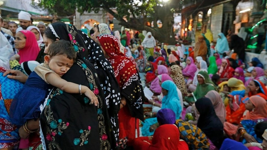 A child sleeps as devotees gather for evening prayers at the spot of the 2007 blast at the shrine of Saint Moinuddin Chichi, a Muslim pilgrimage center in Ajmer, Rajasthan, India, Wednesday, March 22, 2017. An Indian court on Wednesday sentenced two Hindu hard-liners to life in prison for triggering an explosion at the Muslim shrine in western India that killed three people and injured more than a dozen a decade ago. (AP Photo/ Deepak Sharma)