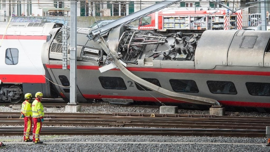 Rescuers stand next to a derailed train in the station of Lucerne, Switzerland, Wednesday, March 22,  2017. Swiss police say they are trying to reach people trapped inside the train in the  city of Lucerne, with details of any injuries still unclear. Rail company SBB says the Milan to Basel train derailed Wednesday as it was pulling out of Lucerne's main train station.   (Urs Flueeler/Keystone via AP)