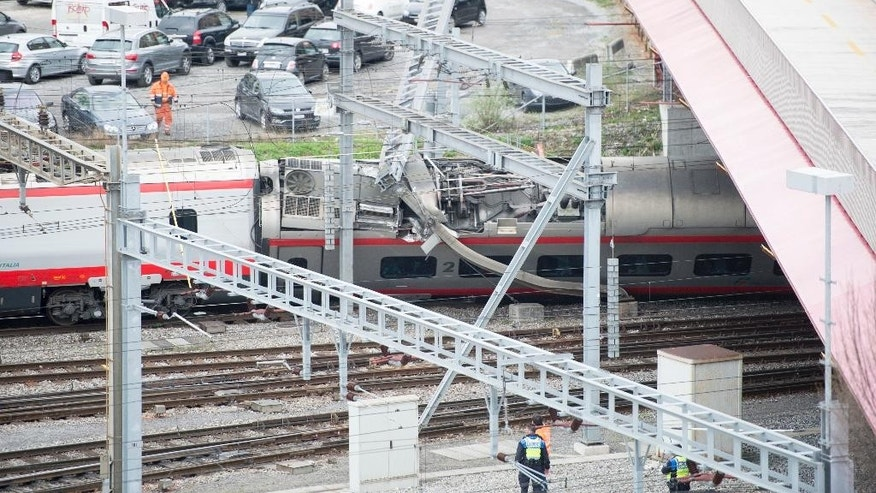 Rescuers stand next to a derailed train in the train station of Lucerne, Switzerland, Wednesday, March 22, 2017. Swiss police say they are trying to reach people trapped inside the train, with details of any injuries still unclear. Rail company SBB says the Milan to Basel train derailed Wednesday as it was pulling out of Lucerne's main train station. (Urs Flueeler/Keystone via AP)