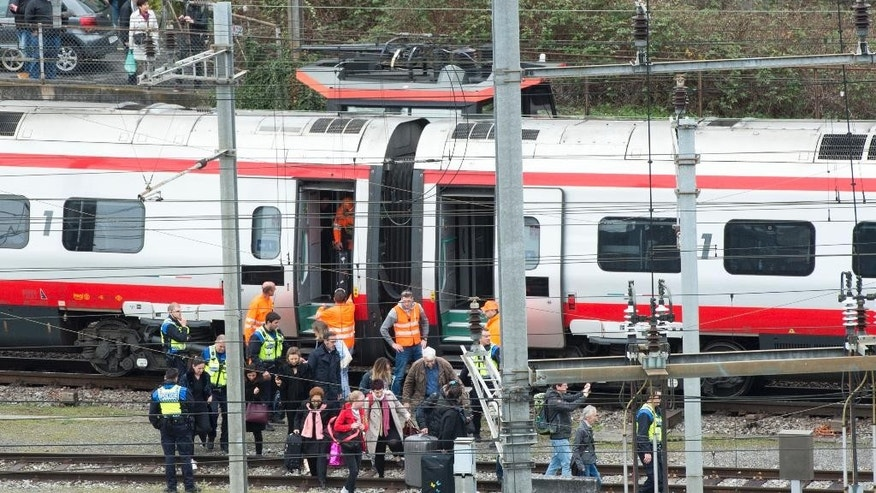 Rescuers stand next to a derailed train and help some passengers in the train station of Lucerne, Switzerland, Wednesday, March 22,  2017. Swiss police say they are trying to reach people trapped inside the train, with details of any injuries still unclear. Rail company SBB says the Milan to Basel train derailed Wednesday as it was pulling out of Lucerne's main train station.   (Urs Flueeler/Keystone via AP)