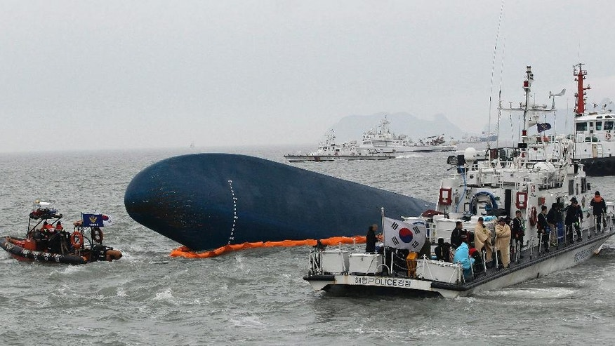 CORRECTS DAY - FILE - In this April 17, 2014 file photo, South Korean Coast Guard personnel search for missing passengers aboard the sunken South Korean ferry Sewol in the water off Jindo, South Korea. Salvage workers are slowly pulling up the huge, corroded South Korean ferry above the sea surface Thursday, March 23, 2017, about three years after it sank on its routine voyage to a resort island, killing more than 300 people, mostly high school students. (AP Photo/Ahn Young-joon, File)