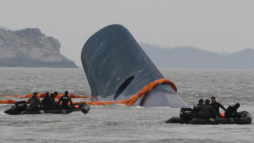 CORRECTS DATE - FILE - In this April 17, 2014 file photo, South Korean Coast Guard personnel search for missing passengers aboard the sunken ferry Sewol in the waters off Jindo, South Korea. Salvage workers are slowly pulling up the huge, corroded South Korean ferry above the sea surface Thursday, March 23, 2017, about three years after it sank on its routine voyage to a resort island, killing more than 300 people, mostly high school students. (AP Photo/Ahn Young-joon, File)