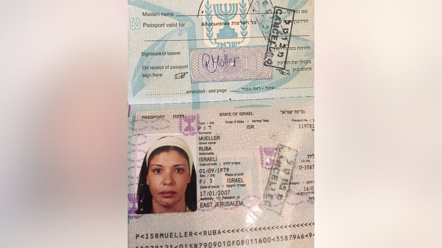 In this Tuesday, March 14, 2017 photo, a cancelled Israeli passport of a Jerusalem born Palestinian Israeli Ruba Mueller, is seen. Ruba was granted a German citizenship based on her marriage. Mueller learned recently that her passport wouldn't be renewed because she had left Israel immediately after obtaining it 10 years ago. She won't lose her citizenship, but has to go back to using a travel document that has to be renewed every two years. (AP Photo/Karin Laub)