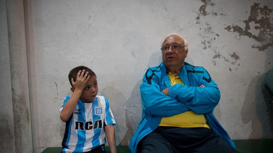 "In this Nov. 11, 2016 photo, head soccer talent scout Ramon Maddoni, of Club Social Parque and Boca Juniors children's division, sits on the bench with young player Benjamin Palandella at the youth soccer academy Club Social Parque in a working class neighborhood of Buenos Aires, Argentina. ""At Club Parque, we work a lot on the fundamentals, the technique. We recognize talent from a young age and our eye has been sharpening with time,"" said Maddoni. (AP Photo/Natacha Pisarenko)"