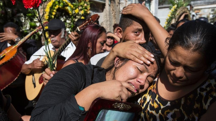 FILE - In this March 17, 2017 file photo, Shirley Palencia weeps during the burial service for 17-year-old sister Kimberly Palencia Ortiz, who died in the Virgen de la Asunción Safe Home fire, at the cemetery in Guatemala City. Authorities said the fire that swept through parts of the institution when mattresses were set ablaze during a protest by girls protesting conditions at the overcrowded youth shelter. (AP Photo/Moises Castillo, File)