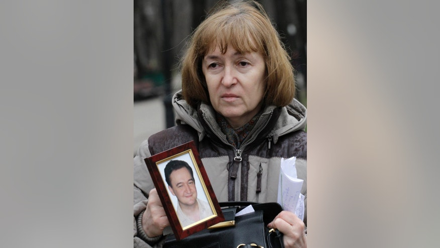 FILE - In this Nov. 30, 2009 file photo, Nataliya Magnitskaya, mother of lawyer Sergei Magnitsky who died in jail, holds a photo of her son as she speaks during an interview with the AP in Moscow. Nilokai Govorkov, the lawyer hired by the family of Sergei Magnitsky, a Russian whistleblower who died in jail, has been injured in a fall from his Moscow apartment Tuesday, March 21, 2017. He is now in hospital with serious head injuries, according to a statement from William Browder, Magnitsky's former employer. (AP Photo/Alexander Zemlianichenko, File)