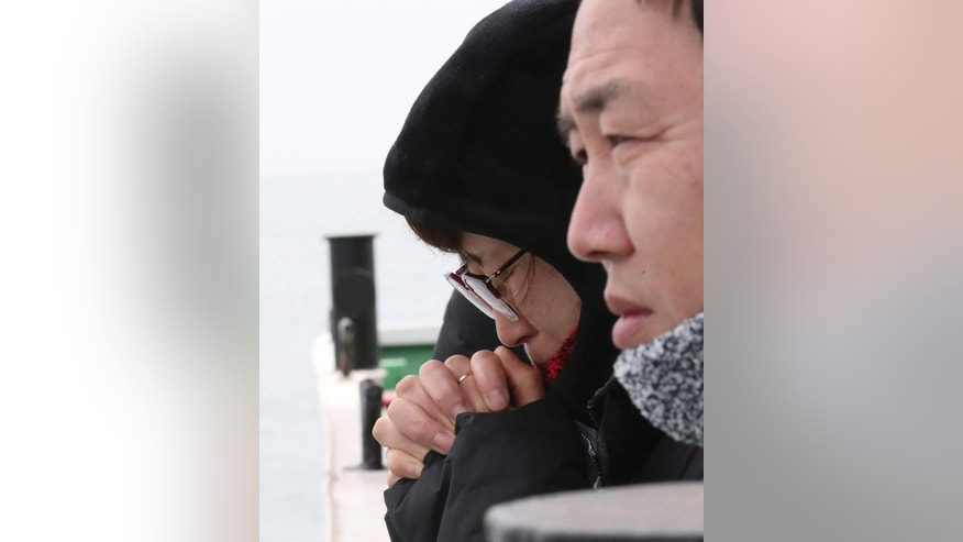 An unidentified relative of missing passengers of sunken Sewol ferry prays as two barges prepare to attempt to salvage the boat in waters off Jindo, South Korea, Wednesday, March 22, 2017. South Korean workers have started tests to determine if they can begin salvaging a 6,800-ton ferry that sank in 2014, killing more than 300 people and triggering the initial public uproar that contributed to the recent ouster of Park Geun-hye as president. (Lee Jin-wook/Yonhap via AP)