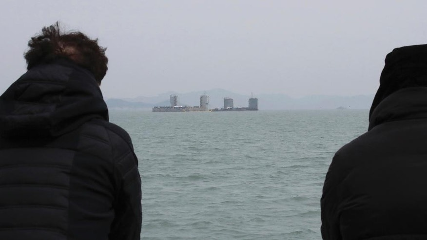 Two barges prepare to attempt to salvage the sunken Sewol ferry as relatives of missing passengers of the boat watch in waters off Jindo, South Korea, Wednesday, March 22, 2017. South Korean workers have started tests to determine if they can begin salvaging a 6,800-ton ferry that sank in 2014, killing more than 300 people and triggering the initial public uproar that contributed to the recent ouster of Park Geun-hye as president. (Lee Jin-wook/Yonhap via AP)