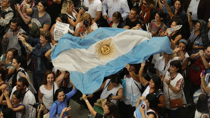 Teachers hold an Argentine flag during a protest demanding higher wages in Buenos Aires, Argentina, Wednesday, March 22, 2017. Tens of thousands of teachers marched to Plaza de Mayo, the park overlooking the presidential palace, during their fourth day of national strike. (AP Photo/Victor R. Caivano)