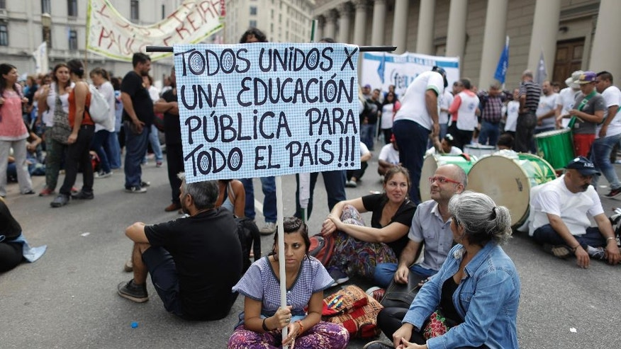 "A teacher holds a sign with a message that reads in Spanish: ""All united for public education for the entire country"", during a protest demanding higher wages in Buenos Aires, Argentina, Wednesday, March 22, 2017. Tens of thousands of teachers marched to Plaza de Mayo, the park overlooking the presidential palace, during their fourth day of national strike. (AP Photo/Victor R. Caivano)"