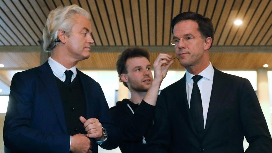 FILE - In this March 13, 2017 file photo, Dutch Prime Minister Mark Rutte, right, and right-wing populist leader Geert Wilders, get their microphones installed prior to a national televised debate in Rotterdam, Netherlands. Wilders said on Wednesday, March 22, 2017, that political parties discussing the makeup of the next Dutch ruling coalition are shutting him out and sidelining 1.3 million people who voted for his party in last week's parliamentary election. (Yves Herman/Pool via AP, File)