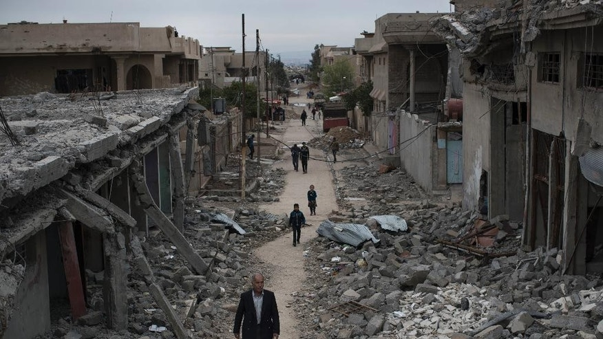 Iraqi civilians walk in a neighborhood recently liberated by Iraqi security forces on the western side of Mosul, Iraq, Wednesday, March 22, 2017. (AP Photo/Felipe Dana)