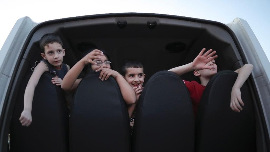 In this March 13, 2017, Syrian migrants Fadi, from left to right, Judy, Hosip and Mikl, wave from the back of a vehicle in La Punta, Argentina. The United Nations' child relief agency recently said that 2016 was the worst yet for Syrian young people, with at least 652 children killed. (AP Photo/Nicolas Aguilera)