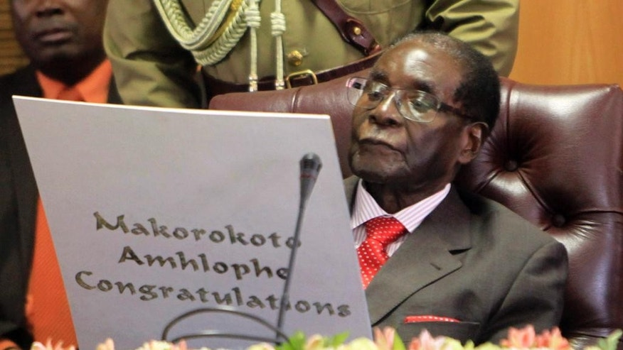 "FILE -- In this Tuesday, Feb. 21, 2017 file photo, Zimbabwean president Robert Mugabe reads his birthday card as he marks his 93rd birthday at his offices in Harare. Mugabe might be slowing down but his busy foreign travel schedule has led the opposition to call him the ""non-resident president."" (AP Photo/Tsvangirayi Mukwazhi, File)"