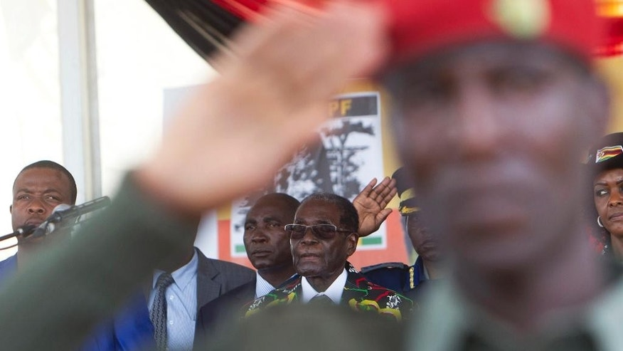 "FILE -- In this Saturday, Feb. 25, 2017 file photo Zimbabwean President Robert Mugabe, center, attend his 93rd Birthday celebrations in Matopos near Bulawayo, Zimbabwe. Mugabe might be slowing down but his busy foreign travel schedule has led the opposition to call him the ""non-resident president."" (AP Photo/Tsvangirayi Mukwazhi, File)"