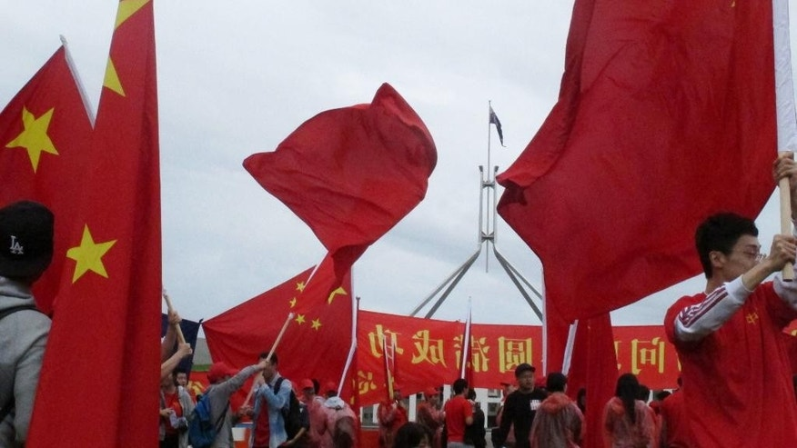 Pro-China demonstrators gather outside Parliament House in Canberra, Australia Thursday, March 23, 2017, ahead of the arrival of Chinese Premier Li Keqiang. Li's visit to Australia and New Zealand is the first by a Chinese premier in 11 years. (AP Photo/Rod McGuirk)