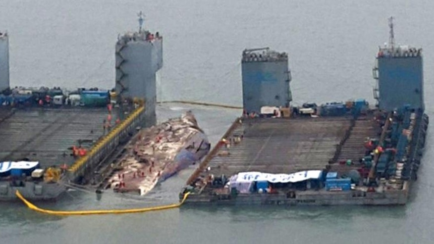 In this photo provided by West Regional Headquarters Korea Coast Guard, workers prepare to lift the sunken Sewol ferry, center, in waters off Jindo, South Korea, Thursday, March 23, 2017. A 6,800-ton South Korean ferry emerged from the water on Thursday, nearly three years after it capsized and sank into violent seas off the country's southwestern coast, an emotional moment for the country that continues to search for closure to one of its deadliest disasters ever. (West Regional Headquarters Korea Coast Guard via AP)