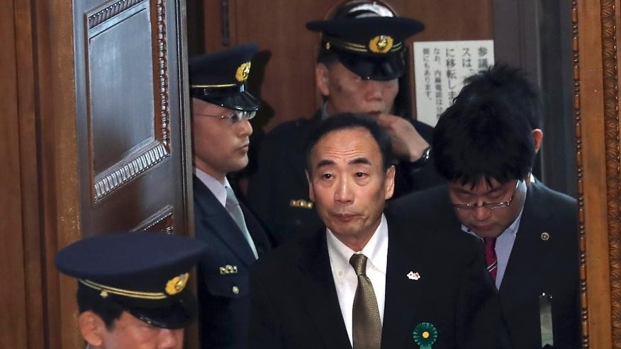 Yasunori Kagoike, center, head of an ultra-nationalistic Japanese school operator, walks in to testify before an upper house panel at the parliament in Tokyo, Thursday, March 23, 2017. Kagoike, at the center of a land and political scandal, testified in parliament that Prime Minister Shinzo Abe donated 1 million yen ($9,000) through his wife for an elementary school where she once was honorary principal. Abe has denied the donation or any influence in the scandal stemming from a questionable 2016 state property sale to Kagoike. (AP Photo/Eugene Hoshiko)