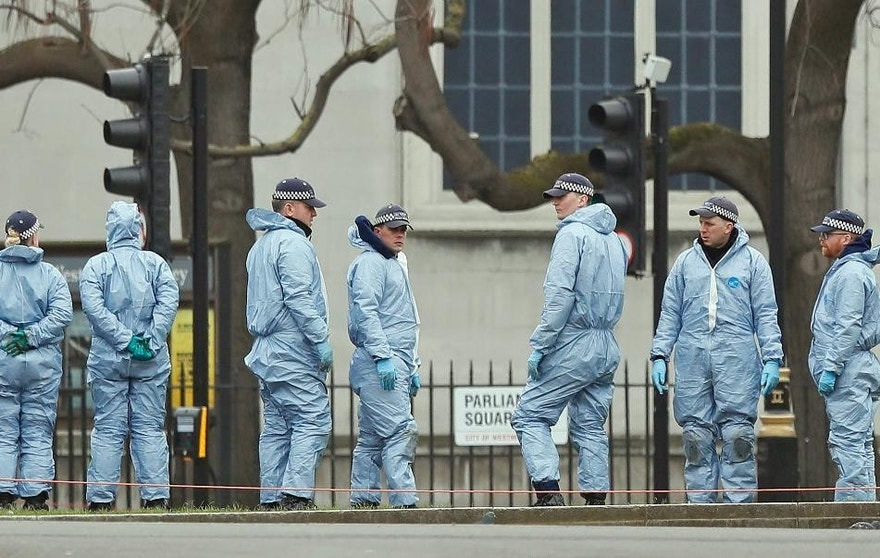 Police forensic officers work in Parliament Square outside the Houses of Parliament in London, Thursday March 23, 2017. On Wednesday a knife-wielding man went on a deadly rampage, first driving a car into pedestrians then stabbing a police officer to death before being fatally shot by police within Parliament's grounds in London. (AP Photo/Kirsty Wigglesworth)