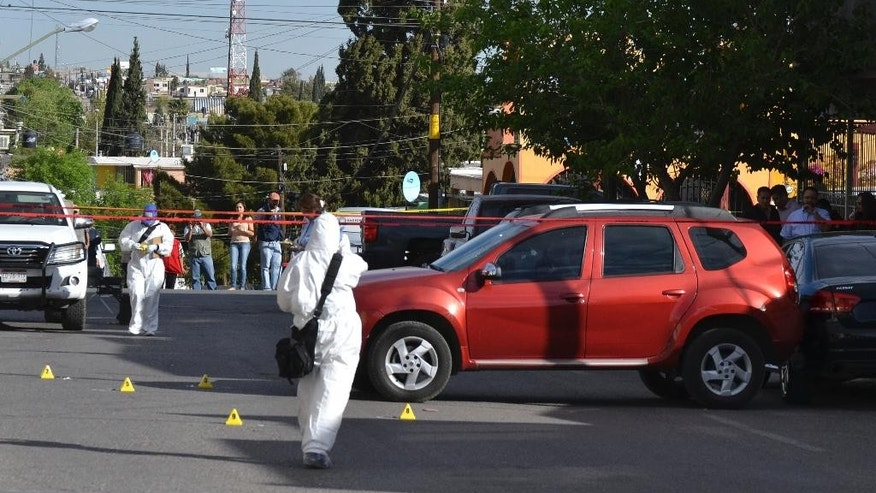 Forensic workers work on the scene where journalist Miroslava Breach was shot and killed outside her home in Chihuahua, Mexico, Thursday, March 23, 2017.  Breach was gunned down in the northern state of Chihuahua on Thursday, becoming the third journalist to be killed this month in one of the most dangerous countries for media workers. (El Diario de Chihuahua via AP)