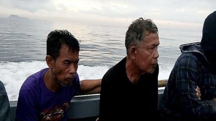 This photo provided by the Command Public Information Office, Western Mindanao Command, Malaysian hostages Tayudin Anjut, left, and Abdurahim Bin Sumas ride a boat after being rescued by marines in Sulu province, southern Philippines on Thursday March 23, 2017. Two Malaysian sailors held captive for eight months by Muslim militants were rescued Thursday in the southern Philippines, military officials said. (Command Public Information Office, Western Mindanao Command via AP)