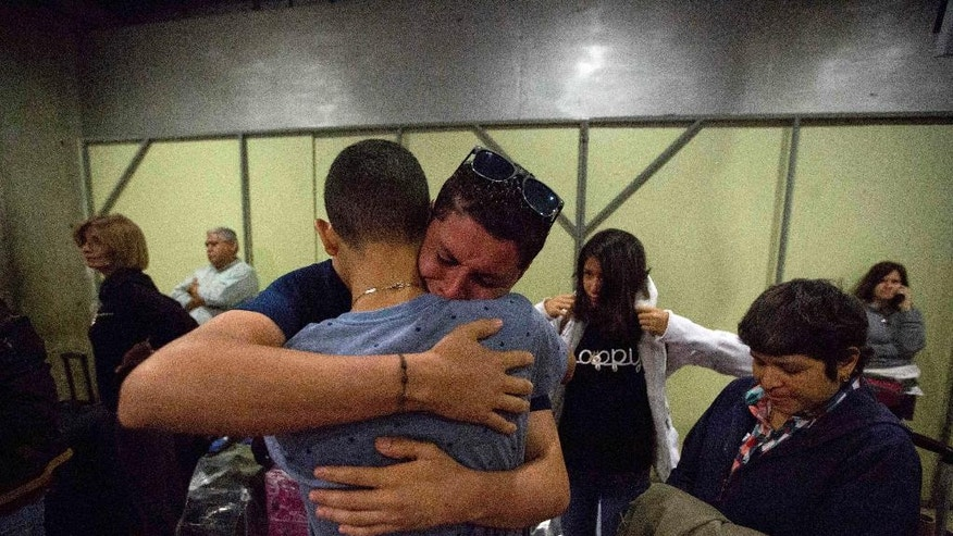 "In this March 17, 2017 photo, Jose Luis Garcia embraces and cries as he says goodbye to his little brother that departs to Bogota on his way to Israel, at the Simon Bolivar International Airport in Maiquetia, Venezuela. The protracted fight over the so-called ""Venezuela Nine"" religious converts on their way to Israel underscores the fierce debate in a divided Israeli society over who is a Jew and how a religion that doesn't proselytize like Christianity or Islam embraces an increasing number of converts, especially from Latin America, who have found their way to Judaism outside traditional paths like marrying someone of the faith. (AP Photo/Fernando Llano)"