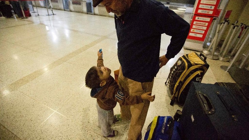 In this March 17, 2017 photo, Franklin Perez speaks with his son Ezra as they wait for a flight to Bogota on their way to Israel, at the Simon Bolivar International Airport in Maiquetia, Venezuela. Perez freely admits that if it weren't for Venezuela's collapse they would've never looked to move to Israel. (AP Photo/Fernando Llano)