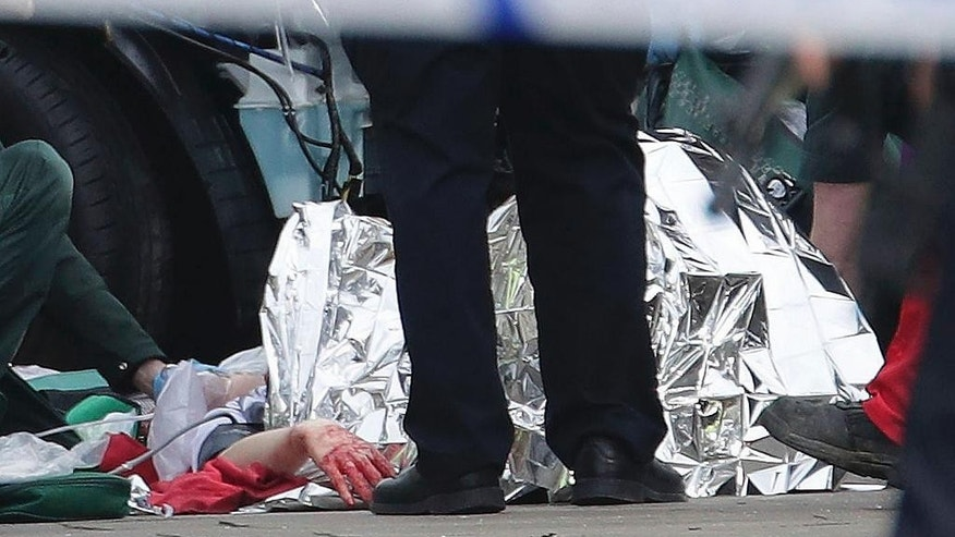 "Emergency personnel tend to an injured person close to the Palace of Westminster, London, Wednesday, March 22, 2017. London police say officers called to a 'firearms incident' on Westminster Bridge, near Parliament. The leader of Britain's House of Commons says a man has been shot by police at Parliament. David Liddington also said there were ""reports of further violent incidents in the vicinity."" London's police said officers had been called to a firearms incident on Westminster Bridge, near the parliament. Britain's MI5 says it is too early to say if the incident is terror-related. (Yui Mok/PA via AP)."