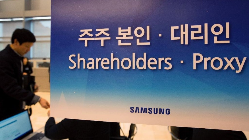 A shareholder stands behind a signage for the Samsung Electronics Co. annual general meeting at the company's Seocho office building in Seoul, South Korea, Friday, March 24, 2017. (SeongJoon Cho/Pool Photo via AP)