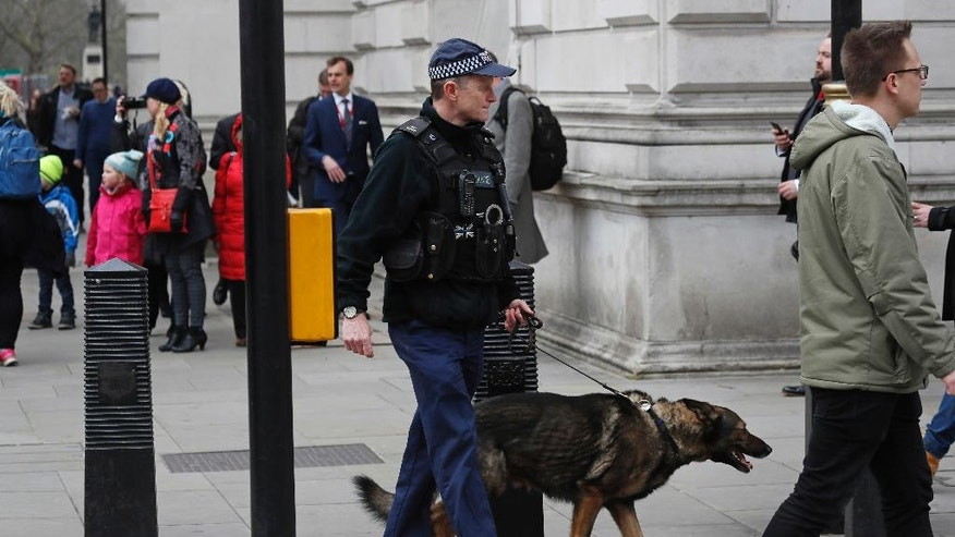 A police dog handler patrols on a road near the Houses of Parliament in London, Thursday March 23, 2017 on her way to the House of Parliament. On Wednesday a man went on a deadly rampage, first driving a car into pedestrians then stabbing a police officer to death before being fatally shot by police within Parliament's grounds in London. (AP Photo/Kirsty Wigglesworth)