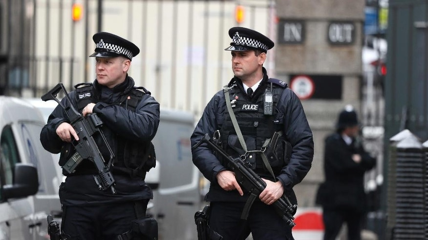 Armed police officers stand guard near the Houses of Parliament in London, Thursday March 23, 2017 on her way to the House of Parliament. On Wednesday a man went on a deadly rampage, first driving a car into pedestrians then stabbing a police officer to death before being fatally shot by police within Parliament's grounds in London. (AP Photo/Kirsty Wigglesworth)