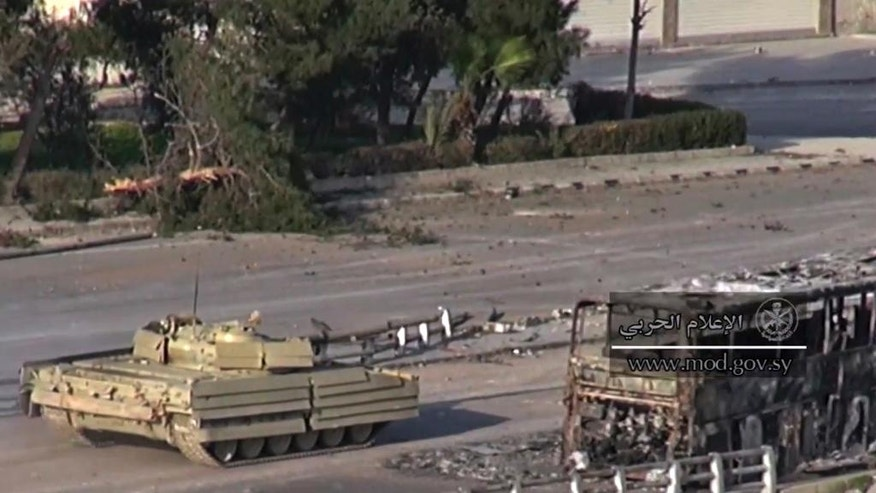 This frame grab from video provided by the government-controlled Syrian Central Military Media, shows a tank of Syrian troops passing by the remains of a burned bus, in an eastern neighborhood of Damascus, Syria, Wednesday, March. 22, 2017. Syrian troop are engaged in fighting with insurgents who have tried to breach government lines in eastern neighborhoods of the capital this week. The operation is spearheaded by the al-Qaida-linked Levant Liberation Committee. (Syrian Central Military Media, via AP)