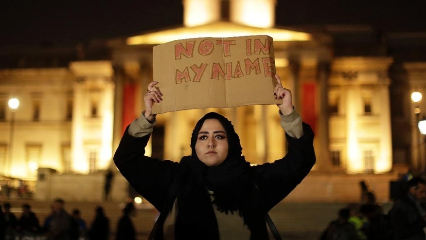 A woman holds up a sign at a vigil for the victims of Wednesday's attack, at Trafalgar Square in London, Thursday, March 23, 2017. The Islamic State group has claimed responsibility for an attack by a man who plowed an SUV into pedestrians and then stabbed a police officer to death on the grounds of Britain's Parliament. Mayor Sadiq Khan called for Londoners to attend a candlelit vigil at Trafalgar Square on Thursday evening in solidarity with the victims and their families and to show that London remains united. (AP Photo/Matt Dunham)
