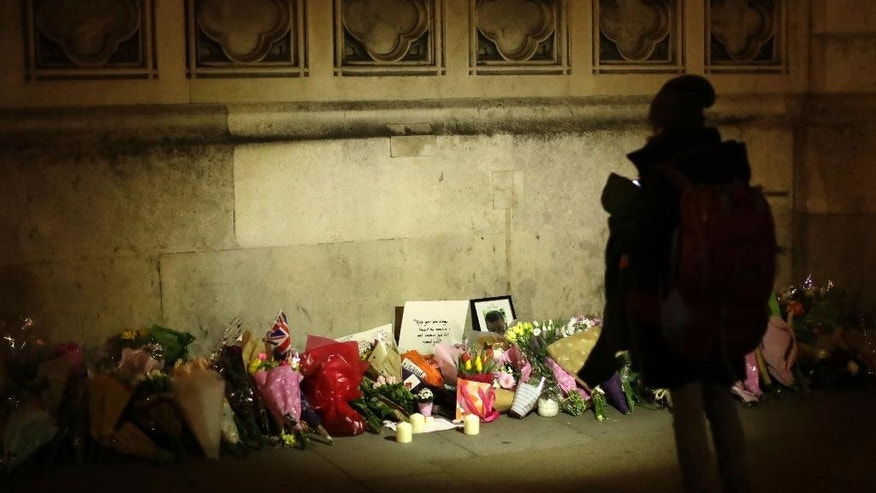 People lay flowers as a tribute to the victims of Wednesday's attack outside the Houses of Parliament, after police cordon was removed in central London, Thursday March 23, 2017.  Authorities on Thursday identified a 52-year-old Briton as the man who mowed down pedestrians and stabbed a policeman to death outside Parliament in London, saying he had a long criminal record and once was investigated for extremism — but was not currently on a terrorism watch list. (AP Photo/Matt Dunham)