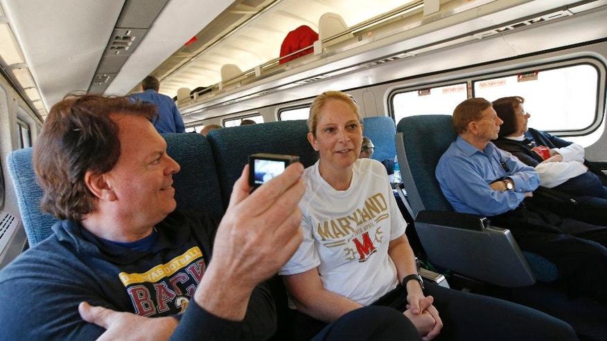 Maryland coach Brenda Frese, center, conducts an interview for a school staff member on board Amtrak Regional as the team headed from Baltimore to Stamford, Conn., Thursday, March 23, 2017. Frese wants to give her team new experiences so the two-time Big Ten Coach of the Year decided to have the Terrapins take the train instead of a bus to the Bridgeport Regional of the NCAA women's college basketball tournament. Freeze's parents, right, joined the trip. (AP Photo/Kathy Willens)