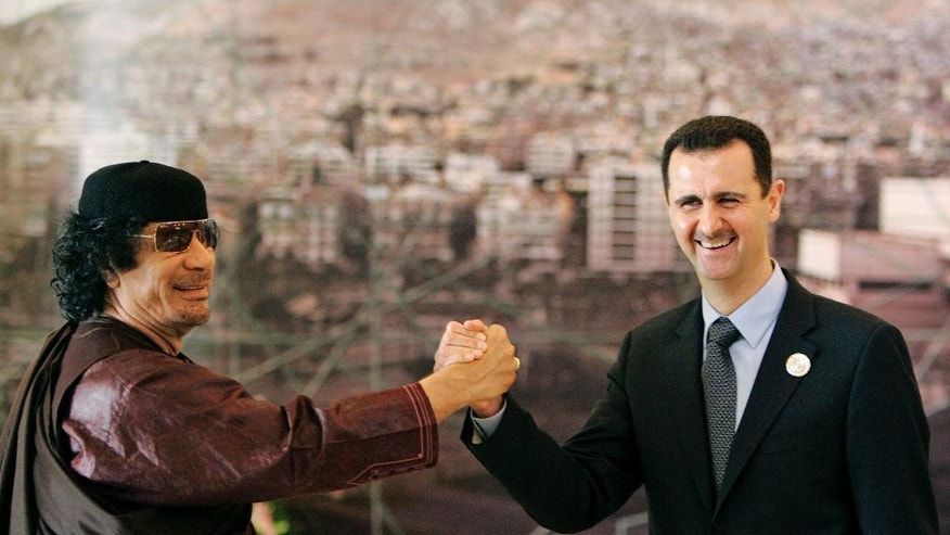 FILE - In this March 2008 file photo, Libyan leader Moammar Gadhafi, left, clasps hands with Syrian President Bashar Assad, right, during the opening session of the Arab Summit in Damascus, Syria. Egypt's ousted former leader Hosni Mubarak is released after six years in prison, but he is not the only ruler in the Middle East to be caught up in Arab Spring uprisings that swept across the region since 2011. Exiled, killed or fighting for survival, here's a look at the fate of other Arab leaders and where they are now. (AP Photo/Hussein Malla, File)
