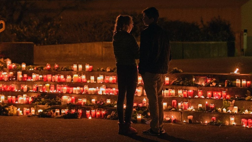 FILE - In this March 24, 2015 file photo students stand near candles in front of the Joseph-Koenig Gymnasium in Haltern, Germany. Students of this school were among the victims of of the Germanwings plane that crashed in the French Alps. Germanwings co-pilot Andreas Lubitz deliberately crashed the jet on March 24, 2015, killing all 150 people on board. Guenter Lubitz, the father of the Germanwings pilot says his son couldn't have committed such an act. He plans a press conference Friday March 24, 2017. (AP Photo/Martin Meissner, file)