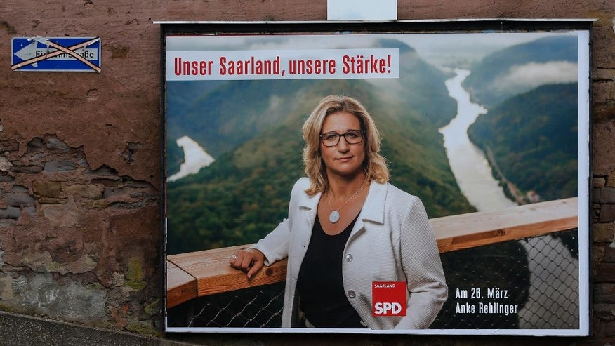 In this March 23, 2017 photo an election poster showing Saarland's Social Democrats, SPD, top candidate Anke Rehlinger hangs at the wall of a house in St.Wendel, Germany. Federal state elections of Saarland state will be held next Sunday. (AP Photo/Michael Probst)