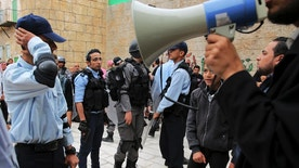 """In this Wednesday, March 22, 2017 photo, a director gives instructions to the actors dressed as Israeli policemen during a shoot of the """"Heaven's Gate"""" movie in a recreated alleyway of Jerusalem's Old City in Khan Younis, Gaza Strip. The set is the latest effort by the al-Aqsa channel, run by Gaza's Islamic militant Hamas rulers, to kick-start its drama production in the territory. (AP Photo/Adel Hana)"""