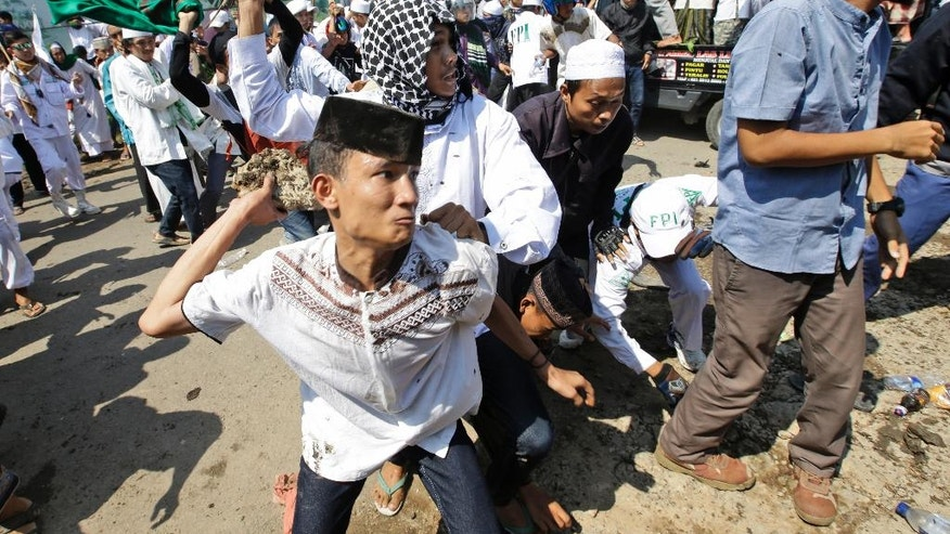 A man throws a rock at police officers during a Muslim hardliner protest against the construction of a Catholic church in Bekasi, Indonesia, Friday, March 24, 2017. Indonesian police fired tear gas to disperse the protesters as they tried to force their way into the Santa Clara church, which has been under construction since November. (AP Photo/Achmad Ibrahim)