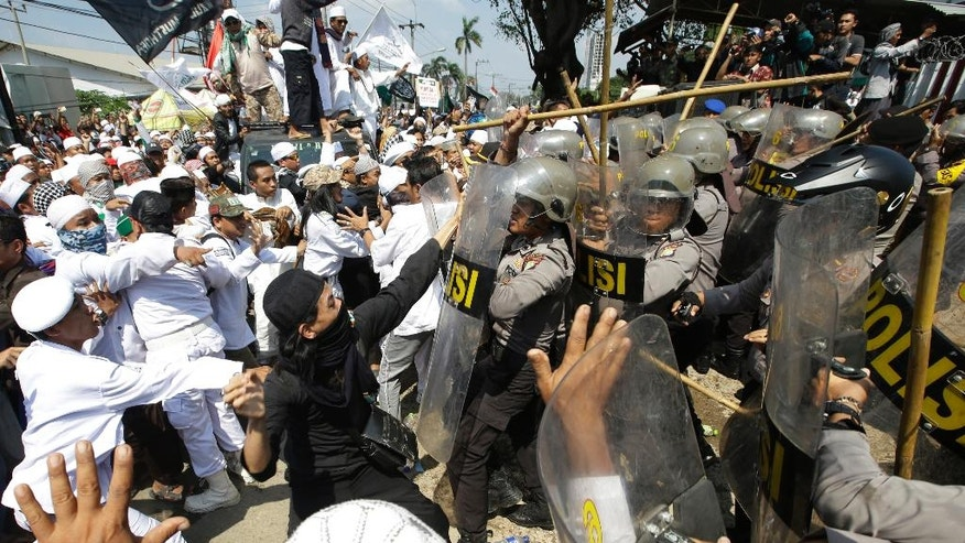 Police officers clash with Muslim hardliners during a protest against the construction of a Catholic church in Bekasi, Indonesia, Friday, March 24, 2017. Indonesian police fired tear gas to disperse the protesters as they tried to force their way into the Santa Clara church, which has been under construction since November. (AP Photo/Achmad Ibrahim)