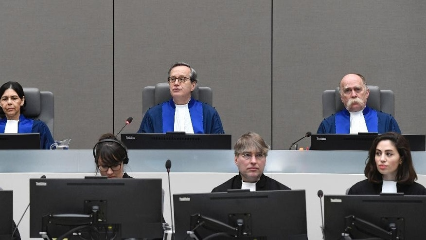 Presiding Judge Marc Perrin de Brichambaut, center, Judge Olga Herrera-Carbuccia, left, and Judge Peter Kovacs, right, are about to deliver the court's order for reparations to victims in the Germain Katanga case at the International Criminal court in The Hague, Netherlands, Friday March 24, 2017. (Toussaint Kluiters POOL via AP)