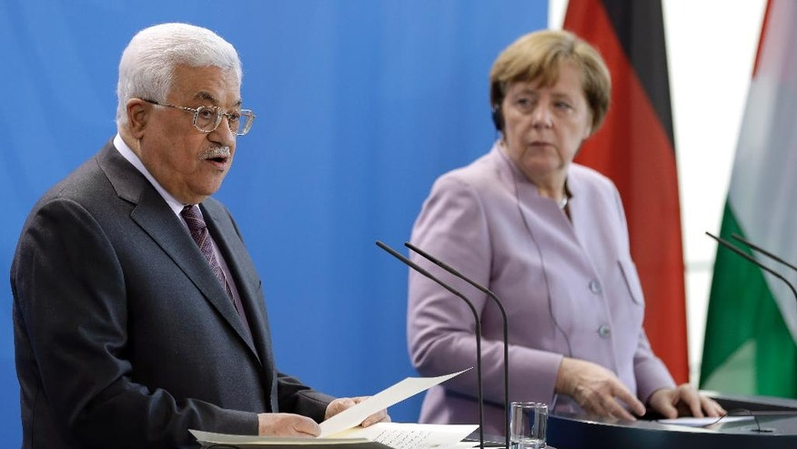 German Chancellor Angela Merkel, right, and Palestinian President Mahmoud Abbas, left, address the media during a joint news conference prior to a meeting at the chancellery in Berlin, Germany, Friday, March 24, 2017. (AP Photo/Michael Sohn)