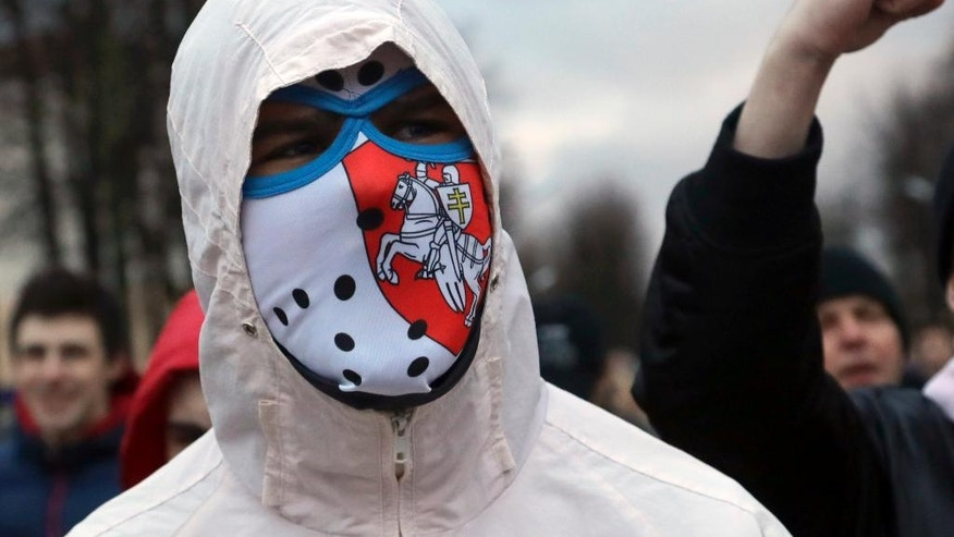 In this photo taken on Friday, March 10, 2017, Evgeny Radkevich with face covered by a balaclava, shouts slogans at a rally in the town of Maladzyechna, 60 kilometers (35 miles) northwest of the capital Minsk, Belarus. Radkevich, 19-year-old unemployed repairman, just freed from a seven-day jail stay after being arrested in a protest, thinks he did the right thing. Belarus' unemployed are caught between an array of unsavory options and their feeling of being trapped is fueling an unusual wave of protests against the authoritarian regime. (AP Photo/Sergei Grits)