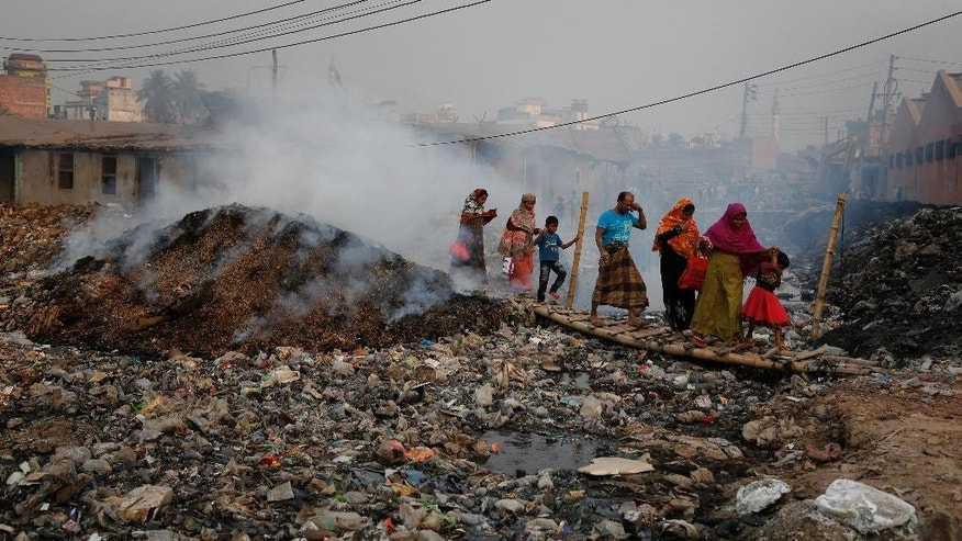 In this Monday, Feb. 6, 2017 photo, Bangladeshi people walk across a temporary bridge as smoke emits from tannery waste at the highly polluted Hazaribagh tannery area in Dhaka, Bangladesh. Pure Earth a nongovernmental organization that addresses industrial pollution put Hazaribagh on its Top 10 list of polluted places, along with Chernobyl, although similar problems of pollution and dangerous working conditions exist at tannery clusters in the Philippines and India as well. (AP Photo/A.M. Ahad)